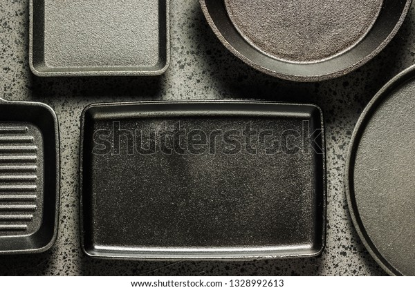 Various cast iron skillets and pans on dark background. Selective focus, space for text.