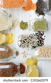 Various cereals, grains and beans in glass jars. Lentils, chickpeas, peas, beans, quinoa, rice, bulgur and buckwheat. Concept  Clean eating. White wooden background