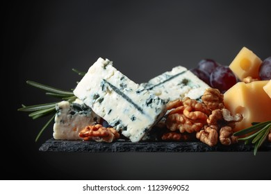 Various cheeses , grapes and walnuts on a dark background.