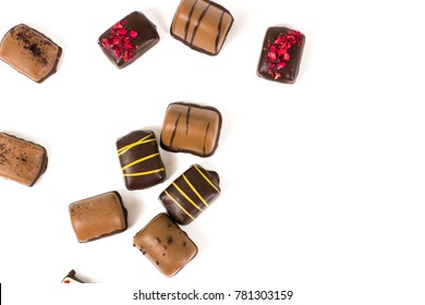 Various of chocolate candies lies on the white background in chaotic order.