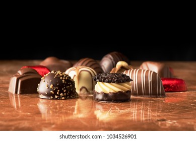 Various chocolate candies on a marble background