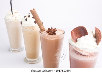 various chocolate and coffee with cream smoothies placed diagonally on white background