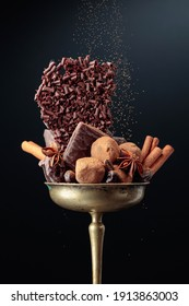 Various chocolates with ingredients.  In an old brass bowl candy, coffee beans, cinnamon, anise, and pieces of broken black chocolate. Copy space.