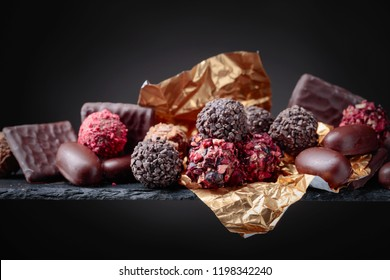 Various chocolates on a black background. Copy space.