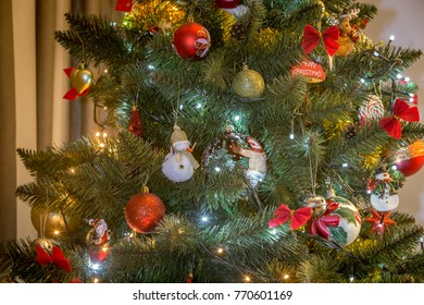 Various Christmas decorations on a tree in a home.