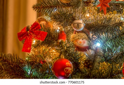 Various Christmas decorations on a tree in a home. Hidden snowman ornament.