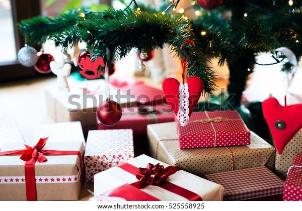 Various Christmas presents under the illuminated Christmas tree.