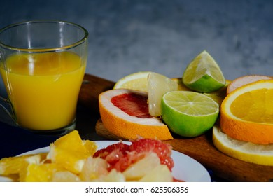 Various citrus fruit cut into slices orange, lemon, lime, grapefruit, pomelo and a glass of orange juice. Spread out on a wooden board and a vintage white plate