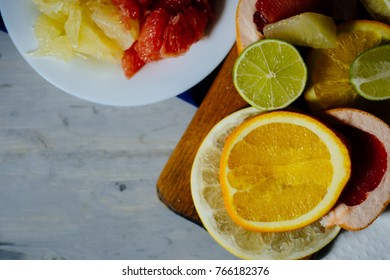 Various citrus fruit cut into slices orange, lemon, lime, grapefruit, pomelo and a glass of orange juice. Spread out on a wooden board and a vintage white plate on the background of natural