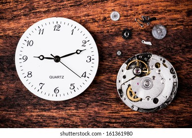 Various clock parts (cogs, hands, springs) laid on a rustic/antique wood background, viewed from above