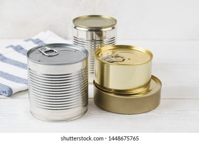 Various closed tin cans with food preserves on a light gray background. Canned food concept. Food donations. Copy space.
