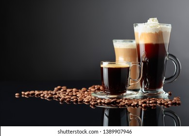 Various coffee drinks and coffee beans on black reflective background. Copy space.