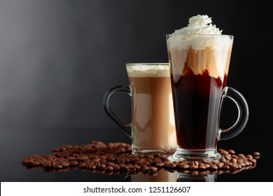Various coffee drinks on black reflective background. Latte and Irish coffee in glass mugs. Copy space.