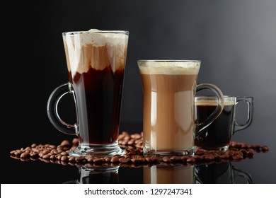 Various coffee drinks on black reflective background.