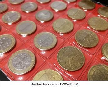 Various coins in the numismatics album close up. Hobby of numismatics