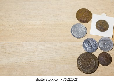 Various coins on a wooden table with magnifying glass, numismatic materials and an album for coins - Numismatic scene. Wooden background.