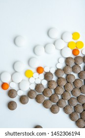 Various color pills are scattered on white background. Drugs and supplements concept