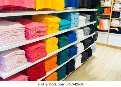 Various color T-shirts at shelf, colorful shirts folded in store.