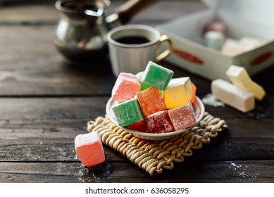 Various color turkish delight lokum with powdered sugar on little plate. Cup of coffee and cezve on background