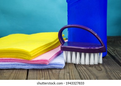 Various colored cleaning wipes, a brush and a bottle of cleaning agent. Items for cleaning the room are placed on a wooden table. The concept of chmstota, cleaning.