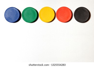 Various colored magnets on metal wall with copy space