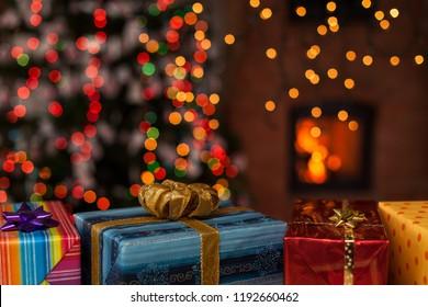 Various colorful christmas presents in front of xmas tree and fireplace
