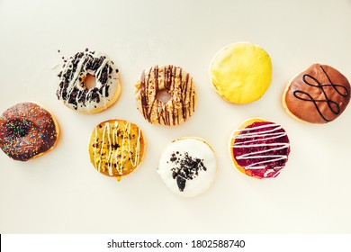 Various colorful creamy donuts with different glaze on top of them, isolated on white background.