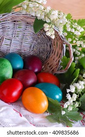 various colorful easter eggs and punnet  with may-lily flower