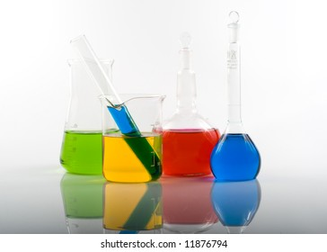 Various colorful flasks over white background