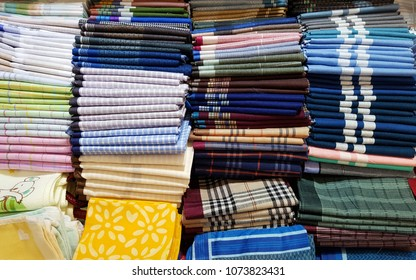 Various colorful folded handkerchiefs that put on the shelf in the fashion market.