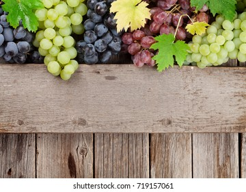 Various colorful grapes on wooden background. With space for your text
