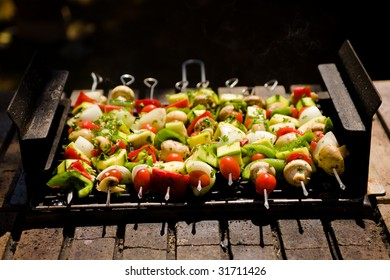 Various colorful and healthy vegetables grill in a barbecue. Shish kebabs made with mushrooms,peppers,cherry tomatoes,zucchini squash, and onions.