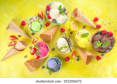 Various colorful ice cream balls in different bowls, with ice cream waffles cones and flavor ingredients - pistachio nuts, berries, lemon, chocolate, vanilla, mint. Trendy yellow bright background