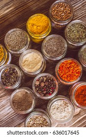Various colorful kinds of spices on rustic wooden table, top view
