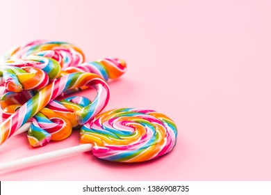 Various colorful lollipops on pink background.