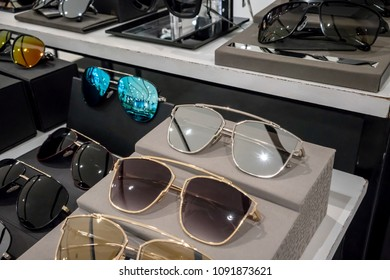 Various of colorful sun glasses in the shop display shelves. Selective focus