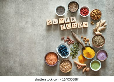 Various colorful superfoods as acai powder, turmeric, matcha green tea, quinoa, pumpkin seeds, blueberry, dried goji berries, cape gooseberries, raw cocoa, hemp seeds and other in bowls
