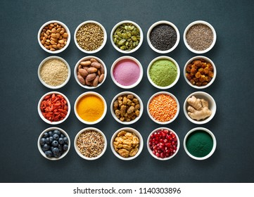 Various colorful superfoods as acai powder, turmeric, matcha green tea, spirulina, quinoa, pumpkin seeds, blueberry, dried goji berries, cape gooseberries, raw cocoa, hemp seeds  on dark background