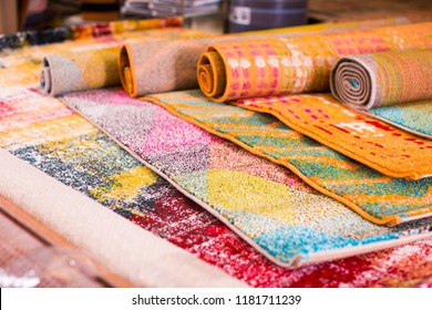 Various colorful wool rugs for sale at store, no people