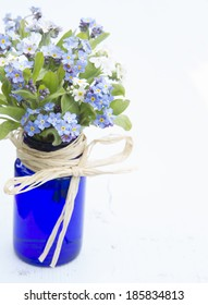 various colors of forget-me-not flowers in a blue vase on a painted white board background