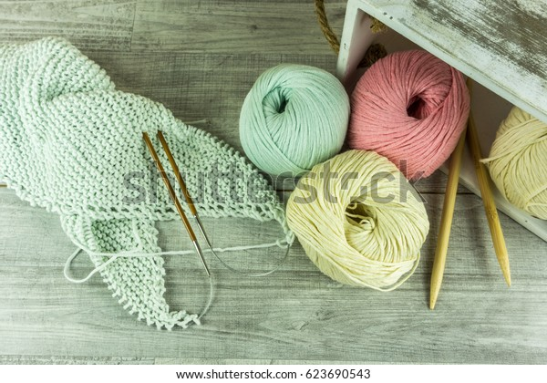 Various colors Wool balls in a wooden box with knitting needles on wooden table