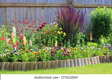 Various Colourful Flowers In A Garden Border With Wooden Fencing And Log Roll Lawn Edging.