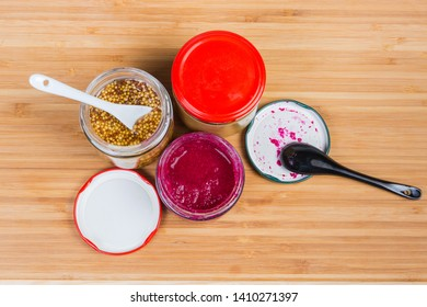 Various condiments - traditional mustard, French mustard and horseradish sauce with red beetroot in small glass jars and ceramic spoons on a bamboo wooden surface, top view