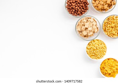Various corn cereals in bowls on white background top view copyspace