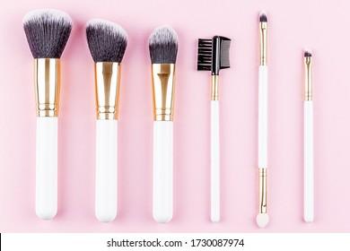 Diverses brosses cosmétiques sur fond rose. Brosses de maquillage pour prendre soin de la peau. Brosses de brosses à flèches bleues à paupières en poudre pour masques professionnels.