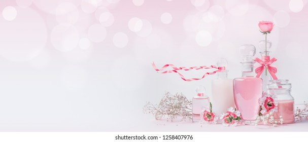 Various cosmetic glass bottles with pink ribbons and flowers standing on white pink background with bokeh, front view, banner or template. Skin care, cosmetic shop, sale and abstract beauty concept