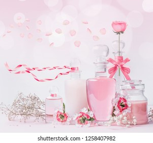Various cosmetic glass bottles with pink ribbons and flowers standing on white pink background with bokeh. Skin care, cosmetic shop, sale and abstract beauty concept