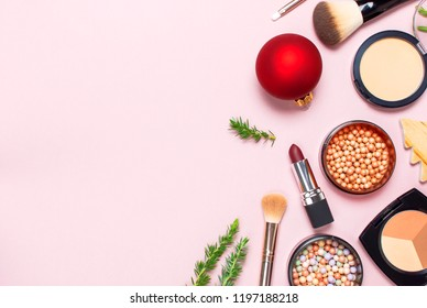 Various cosmetic products for make-up, blusher, powder, brushes, lipstick, eyeshadow and Christmas gift, fir branches, red ball on pink background Flat lay top view New year concept, winter decoration
