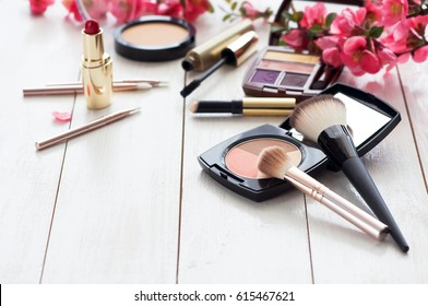 Various cosmetic products for make-up with pink flowers on a white wooden background with copy space.