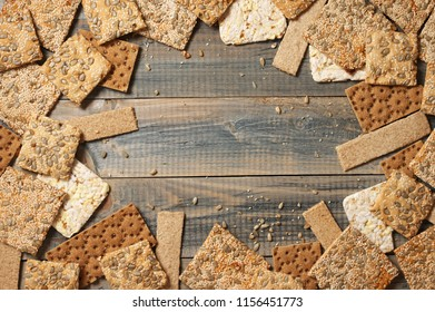 Various crispy wheat, rye and corn flatbread crackers with sesame and sunflower seeds on rustic grey wooden background. Top view point.
